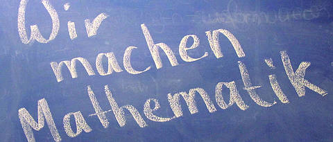 Text on blackboard 'Wir machen Mathematik'