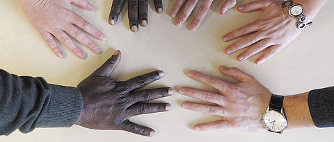 Hands in different skin-colors on a table